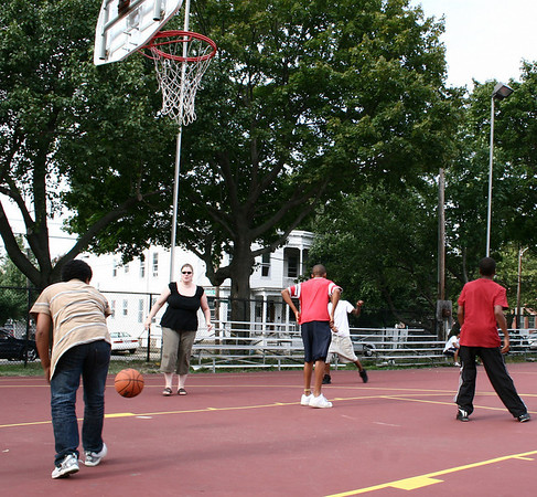Salem: Kathryn Corley, of the Salem Department of Children and Families, plays basketball with neighborhood kids during the cookout at Palmer Cove Park. Photo by Mary Catherine Adams/Salem News.