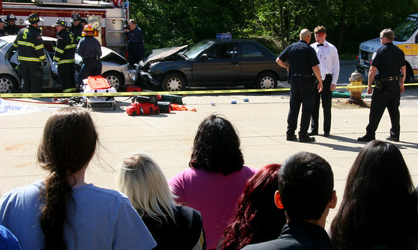 Salem: Salem High School students watch as senior Tom Regan is given a sobriety test by police officers during the school's mock car crash staged to discourage students from drinking and driving. Photo by Mary Catherine Adams/Salem News