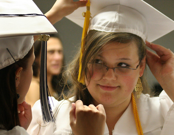Middleton: Wanza Ratcliff, right, gets help adjusting her mortar board from Angilina Pelletier before the start of graduation at North Shore Technical High School on Friday. Photo by Mary Catherine Adams/Salem News