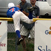 Salem: Danvers' Dan Lynch leaps over the fence while trying to catch a Swampscott home run ball hit in the second inning of the Gallant Memorial Tournament. Photo by Mary Catherine Adams/Salem News.