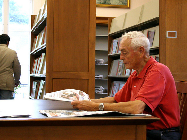 Beverly: Harold Nelson, of Beverly, reads a newspaper in the lobby of the Beverly Public Library as a summer shower passes by outside. Photo by Mary Catherine Adams/Salem News.