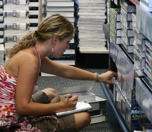 Salem: Cherie Mann, a nursing student at Salem State University, sorts through a large collection of nursing textbooks at the university bookstore. This fall, the bookstore is offering textbooks for rent as well as for purchase. Photo by Mary Catherine Adams/Salem News.<br /> , Salem: Cherie Mann, a nursing student at Salem State University, sorts through a large collection of nursing textbooks at the university bookstore. This fall, the bookstore is offering textbooks for rent as well as for purchase. Photo by Mary Catherine Adams/Salem News.