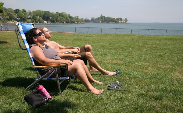 Kate Tyburc, left, and Brett Kelley sunbathe on the grass near Dane Street Beach in Beverly on Tuesday. Photo by Mary Catherine Adams/Salem News<br /> , Kate Tyburc, left, and Brett Kelley sunbathe on the grass near Dane Street Beach in Beverly on Tuesday. Photo by Mary Catherine Adams/Salem News