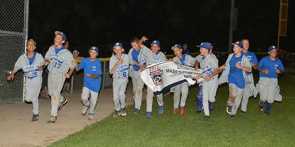 Danvers American Williamsport Team runs the field with the District 15 Campionship Banner after the game.
