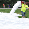 Danvers:<br /> Danvers firefighter Matt Aquaro sprays the fire suppression foam onto the grass field at the fireman's Muster at Endicott Park.<br /> Photo by Ken Yuszkus / Salem News, Wednesday, July 10, 2013.