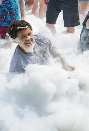 Danvers:<br /> Faissal Ferouni frolics in the fire suppression foam during the fireman's Muster at Endicott Park.<br /> Photo by Ken Yuszkus / Salem News, Wednesday, July 10, 2013.