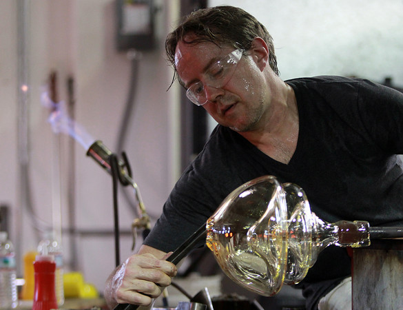 Salem: Chris Watts, a guest artist from the Rosenberg Institute for Passionate and Emerging Artists, uses tongs to create a mouth on a vase during an open glass blowing demonstration at Salem State University's Glassworks Studio on Monday evening. David Le/Salem News