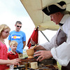 Salem: Graeme Marsden, Regimental Surgeon of the First Foot Guards, shows Megan, 8, Jamie, 6, and Dan Gill the uses of a mortal and pestle during a redcoat encampment at Derby Wharf on Saturday afternoon. David Le/Salem News