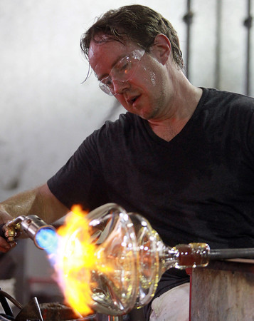 Salem: Chris Watts, a guest artist from the Rosenberg Institute for Passionate and Emerging Artists, uses a blow on the top of a vase during an open glass blowing demonstration at Salem State University's Glassworks Studio on Monday evening. David Le/Salem News