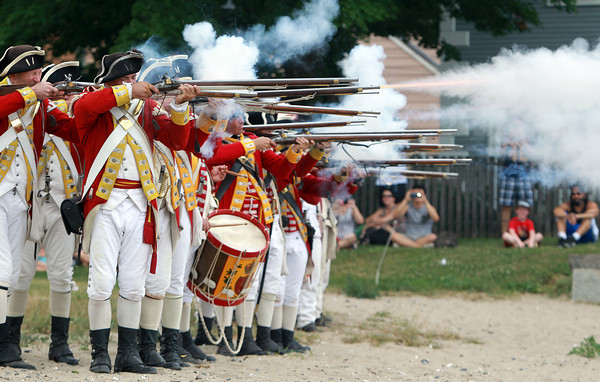 Salem: A troop of redcoats fire shots over Salem Harbor from their encampment site at Derby Wharf on Saturday afternoon. David Le/Salem News