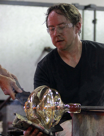 Salem: Chris Watts, a guest artist from the Rosenberg Institute for Passionate and Emerging Artists, uses a special cloth to smooth the glass on the side of a vase during an open glass blowing demonstration at Salem State University's Glassworks Studio on Monday evening. David Le/Salem News