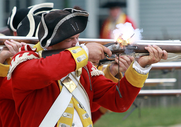 Salem: Edward Scull, of the 10th Regiment of Foot, fires a round of shots over Salem Harbor during a redcoat encampment at Derby Wharf on Saturday afternoon. David Le/Salem News