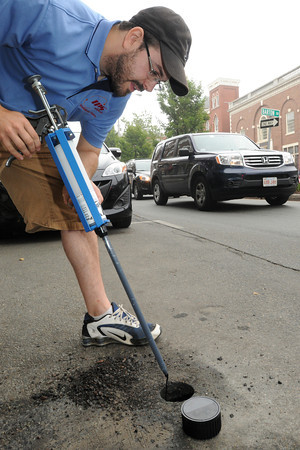 Salem:<br /> James Emery applies epoxy inside the hole cut into the asphalt to glue a sensor at one of the parking spaces on Washington Street. The sensors are installed in the pavement in each parking space. When a car pulls out, it removes all leftover time on the parking meter and resets the meter backto 5 minutes. <br /> Photo by Ken Yuszkus / Salem News, Wednesday, July 10, 2013.