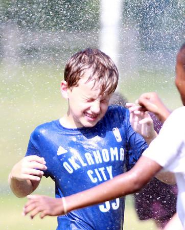 Beverly: Artworks at Waring camper Nick Woods, 12, braces himself while running through a sprinkler on a hot Friday afternoon. David Le/Salem News
