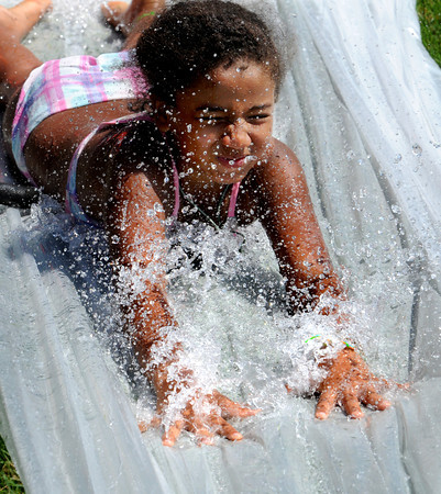 "Beverly:<br /> Valerie Encarnacion slides down the Mad Hatter's water slide on the hill at Lynch Park. She was participating in the Beverly Recreation Department Parks Program. ""Movie stars"" was the theme for the games. 13 parks and 4 camps participated.<br /> Photo by Ken Yuszkus / Salem News, Thursday, July 18, 2013."