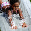 """Beverly:<br /> Valerie Encarnacion slides down the Mad Hatter's water slide on the hill at Lynch Park. She was participating in the Beverly Recreation Department Parks Program. """"Movie stars"""" was the theme for the games. 13 parks and 4 camps participated.<br /> Photo by Ken Yuszkus / Salem News, Thursday, July 18, 2013."""