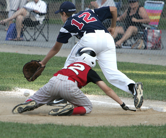 Beverly:<br /> The ball escapes from Middleton's Ryan Manning as Amesbury's Dane Webber gets back to first base after a pop fly was caught for an out at the Amesbury vs Middleton little league game at Harry Ball Field.<br /> Photo by Ken Yuszkus / Salem News, Monday, July 8, 2013.