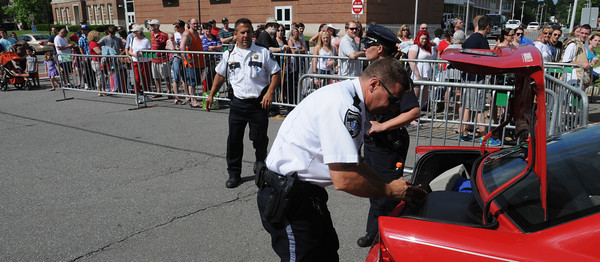 Danvers:<br /> Essex County Sheriff's Department Lt. Tom Cote searches the trunk of a car. In the background people are lined up to be searched before entering Plains Park for the Fourth of July festivities.<br /> Photo by Ken Yuszkus / Salem News, Wednesday, July 3, 2013.
