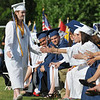 Peabody: Valedictorian Katherine Manzi heads to her seat along a line of high fives after addressing her class.   photo by Mark Teiwes / Salem News