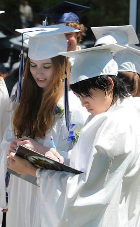 Wenham:<br /> Hamilton-Wenham graduates Sarah Ribet watches Galiya Kolnsberg sign a high school yearbook before the start of their graduation exercise which was held inside the Gordon College Chapel at noon on Sunday.<br /> Photo by Ken Yuszkus/Salem News, Sunday, June 5, 2011.