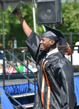 Beverly: Sheilo Andre triumphantly shows off his diploma to the crowd at Beverly High School graduation.  photo by Mark Teiwes / Salem News