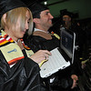 Salem: At the start of the Salem State graduate studies commencement ceremony, Taro Sekimoto, left, Tokyo Japan, video chats with his family back home who were unable to make the trip due to the disaster in Japan.  He and fellow classmate James Picone of Salem, right, are graduating with a MBA.  photo by Mark Teiwes / Salem News