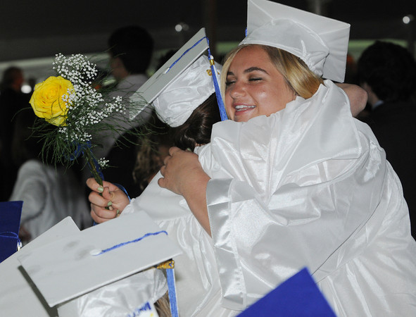 Beverly:<br /> Maxye Cataldo of West Roxbury, left, and Elizabeth Dirico of Hamilton, hug as Elizabeth passes by the seated graduates during the processional at the Landmark School graduation.<br /> Photo by Ken Yuszkus/Salem News, Friday, June 7, 2013.