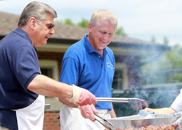 Danvers: Wayne Comeau, left, and John Call, right, grill steak for the Senior Citizen Luncheon at the Danvers Senior Center on Tuesday afternoon. David Le/Salem News
