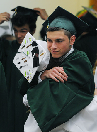 Danvers:<br /> Graduates Kara Neary of Peabody, left, and Ryan Person of Saugus, hug before the start of the Essex Agricultural and Technical High School graduation.<br /> Photo by Ken Yuszkus / Salem News, Thursday, June 6, 2013.