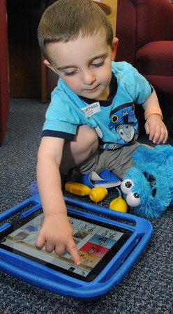 Danvers:<br /> Ben Mover, 2 1/2, of Salem, uses an iPad. Northeast Arc launched it's iPads for Autism campaign to support its Touch to Talk campaign.<br /> Photo by Ken Yuszkus / Salem News, Thursday, June 27, 2013.