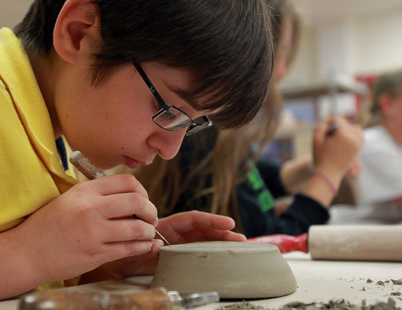 Beverly: Will Emerling, 13, of Salem, concentrates while using a pin tool to inscribe the bottom of a clay bowl he was working on at Clay Dreaming Pottery Studio on Monday afternoon. David Le/Salem News