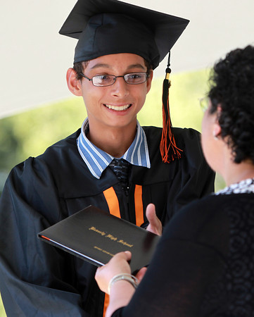 Beverly: Beverly High School graduate Spiro Lustphillips smiles as he receives his diploma from President of the School Committee Maria Decker, on Sunday afternoon. David Le/Salem News