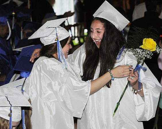 Beverly:<br /> Maxye Cataldo of West Roxbury, left, and Maria Tashjian of Wellsley, hug as Maria passes by the seated graduates during the processional at the Landmark School graduation.<br /> Photo by Ken Yuszkus/Salem News, Friday, June 7, 2013.