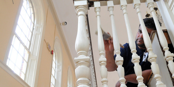 """Salem:<br /> Painter Moses Dolevara paints near the stairway in the """"Great Hall"""" of Salem's Old Town Hall. Gordon College leases the building and is able to repaint the Great Hall because of a recent donation to the Gordon College Institute of Public History.<br /> Photo by Ken Yuszkus / Salem News, Tuesday, June 25, 2013."""