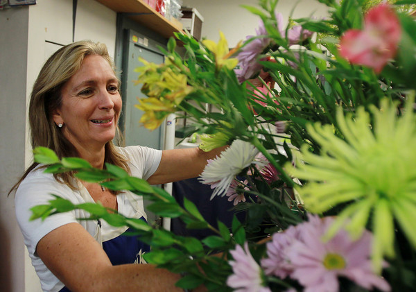 Salem: Betsy Menici, daughter of Peter Barter, has been the shop manager for a few years. She prepares a large floral arrangement on Tuesday afternoon. David Le/Salem News