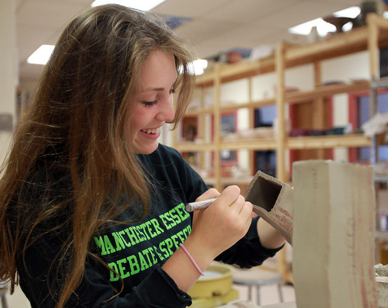 Beverly: Julia Bonaccorso, 15, of Manchester, smiles while making score marks on the bottom of a clay piece she was working on at Clay Dreaming Pottery Studio as part of Afterschool Teens in Clay program. David Le/Salem News