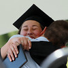 Beverly: Beverly High School graduate Anna Guanci gives her father, Paul, a big hug on stage after he presented her with her diploma on Sunday afternoon. David Le/Salem News