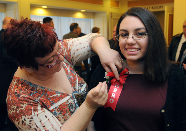 """Danvers:<br /> Angela Romano of Peabody, pins a flower on her daughter, who received the Youth Hero award at the """"Heroes"""" breakfast. The American Red Cross of Northeast Massachusetts honored 12 area residents as its 2013 """"Heroes"""" annual breakfast.<br /> Photo by Ken Yuszkus/The Salem News, Thursday, March 21, 2013."""