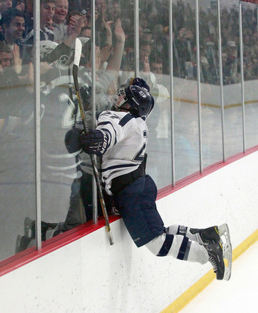 MARY SCHWALM/Staff photo.  St. Johns Prep player James Currier (27) jumps into the glass against his cheering fans after scoring a goal against Central Catholic in their Super 8 game in Stoneham.  3/10/13
