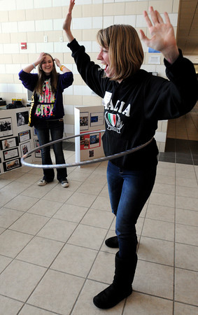 Danvers:<br /> Danvers High seniors Nicole Pszenny, right, and Alicia Tinkham, left, used a hula hoop to win discounts for their choices at the Fun, Fun, Fun table. Danvers High students learned about financial realities at the Reality Check Fair which was held at  North Shore Community College.<br /> Photo by Ken Yuszkus/The Salem News, Monday, March 18, 2013.
