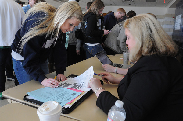 Danvers:<br /> Danvers High senior Lauren Shay, left, is assisted by Dana Sarosy-Horr while figuring how her 401k will work into her imaginary budget at the  Reality Check Fair. Danvers High students learned about financial realities at the fair which was held at  North Shore Community College.<br /> Photo by Ken Yuszkus/The Salem News, Monday, March 18, 2013.