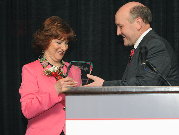 """Danvers:<br /> Patricia Comeau-Simonson receives the Healthcare Hero award from Russell Cole at the """"Heroes"""" breakfast. The American Red Cross of Northeast Massachusetts honored 12 area residents as its 2013 """"Heroes"""" annual breakfast.<br /> Photo by Ken Yuszkus/The Salem News, Thursday, March 21, 2013."""