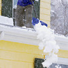 Beverly:<br /> Jeff Glew shovels snow off his roof during the snowstorm on Friday.<br /> Photo by Ken Yuszkus/The Salem News, Friday, March 8, 2013.