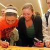 Beverly: Beverly High School juniors Caitlin Harty, Keely Higgins, and Nicole Demars, sign a poster for The One Fund and 2012 BHS graduate Angie Miller at a viewing party on Wednesday evening. David Le/Salem News