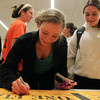 Beverly: Beverly junior Keely Higgins, left, signs a poster supporting 2012 Beverly High graduate Angie Miller and The One Fund, as classmate Nicole Demars looks on, in the hallway outside the auditorium at Beverly High School during a viewing party for American Idol. David Le/Salem News