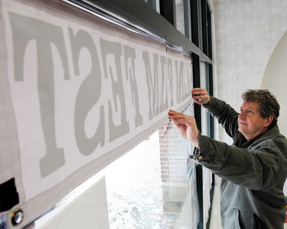 Salem:<br /> Paul Van Ness, co-owner of CinemaSalem and director of Salem FilmFest adjusts the banner in the storefront window at the recently opened space for Salem FilmFest at 188 Essex Street in Salem.<br /> Photo by Ken Yuszkus/The Salem News, Friday, March 1, 2013.