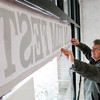 Salem:<br /> Paul Van Ness, co-owner of CinemaSalem and director of Salem FilmFest adjusts the banner in the storefront window at the recently opened space for Salem FilmFest at 188 Essex Street in Salem.<br /> Photo by Ken Yuszkus/The Salem News, Friday, March 1, 2013.