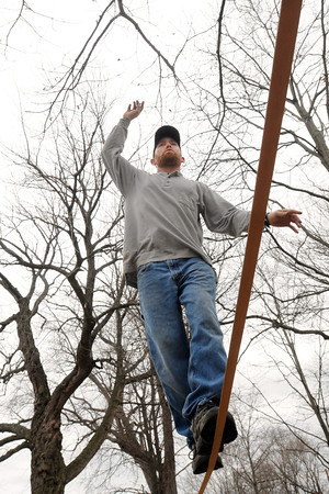 """Salem:<br /> Rusty McStix of Salem walks a 85 foot long slackline which is suspended 6 feet off the ground by being strung between two trees at the Salem Common. He completed a """"full man on site"""" which is walking the full length of the 1 inch line and back without falling.<br /> Photo by Ken Yuszkus/The Salem News, Tuesday, March 5, 2013."""