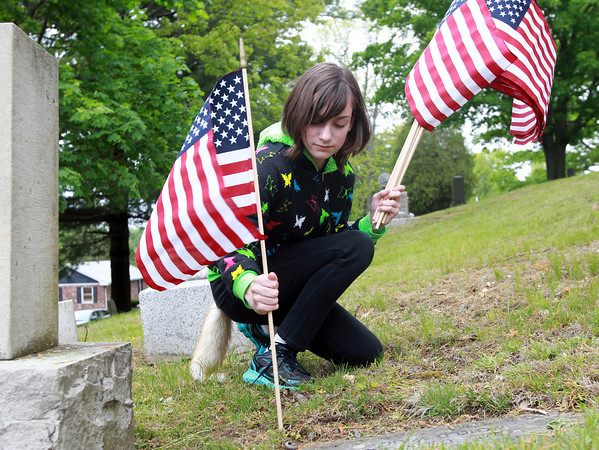 Beverly:Rachel Matthews, 11, of Danvers places a flag in front of the grave of a veteran in Walnut Grove Cemetery on Wednesday afternoon in preparation for Memorial Day. David Le/Salem News