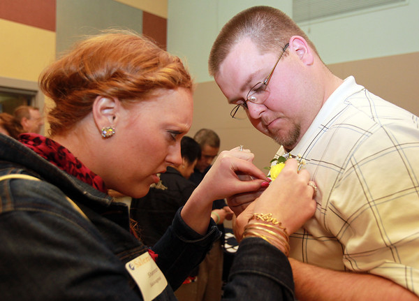Salem: Shannon Sauvageau, of Salem, helps her husband John, pin a boutonniere on his shirt, prior to the start of a ceremony to give out a veteran's stoll for each veteran graduating from Salem State on Wednesday evening. David Le/Staff Photo